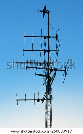 television antenna on blue sky background - stock photo