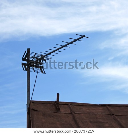 Television antenna over old metal roof on the sky background - stock photo