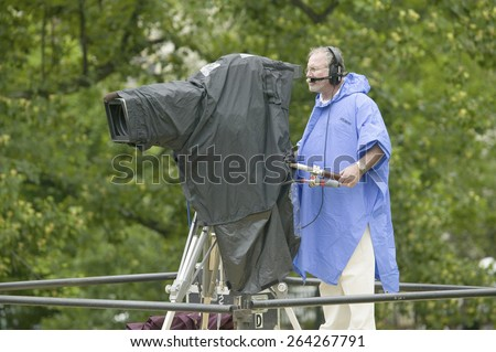 Television cameraman in blue raincoat video taping opening ceremonies of the arrival of Her Majesty Queen Elizabeth II in Richmond Virginia, May 3, 2007 - stock photo