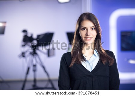 Television presenter recording in news studio.Female journalist anchor presenting business report,recording in television studio.News camera,light equipment behind the scenes. TV program editor. - stock photo