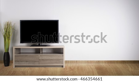 Television put on wood table and wood floor, background white wall.