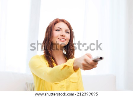 television, relax, home and happiness concept - smiling teenage girl sitting on couch with tv remote control at home - stock photo