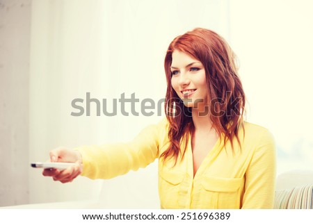 television, relax, home and happiness concept - smiling young woman sitting on couch with tv remote control at home - stock photo