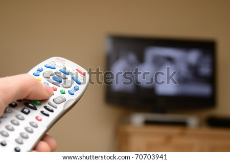 Television remote in the foreground with selective focus and television in the background.