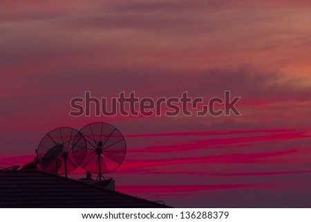 Television Satelite dish on roof in silhouette at sunset - stock photo