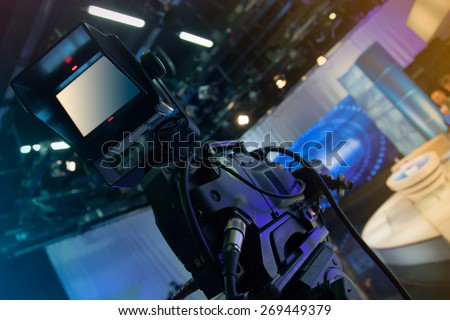 Television studio with camera and lights - recording TV show. Shallow depth of field - focus on camera - stock photo