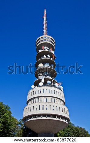 Television tower with antennas and satellite dishes against the blue sky - stock photo