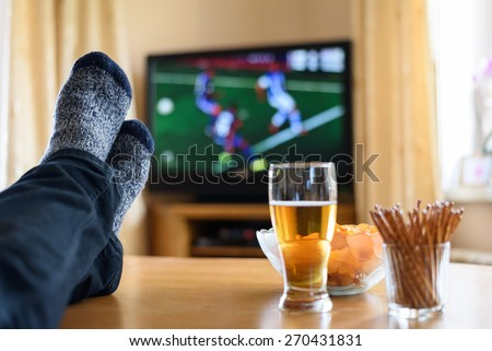 Television, TV watching (football match) with feet on table and huge amounts of snacks - stock photo - stock photo
