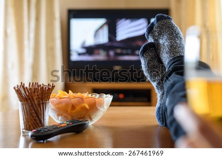 Television, TV watching (movie) with feet on table and huge amounts of snacks - stock photo - stock photo