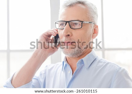 Tell me good news! Serious grey hair senior man in shirt talking on the mobile phone and looking away while standing in front of the window - stock photo