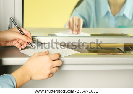 Teller window with working cashier and female hands with claim check. Concept of payment of utilities - stock photo