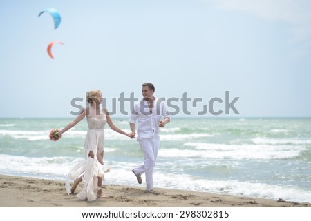 Temder beautiful young wedding couple of boy and girl in white running along ocean beach coast on windy weather sunny day with paraplanes on blue sky background, horizontal picture