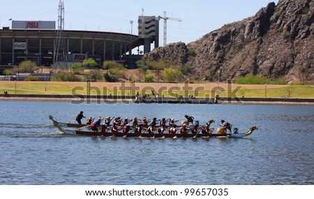 TEMPE AZ - MARCH 31: Two unidentified teams racing along Tempe Town Lake at the Dragon Boat Festival on March 31, 2012. - stock photo