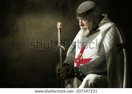 Templar knight praying in a dark background - stock photo