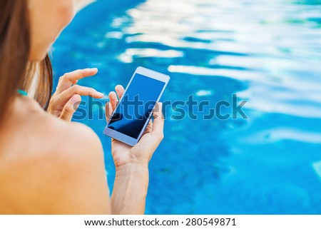 template for a smart phone app: woman using her phone while sitting at poolside - stock photo