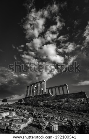 Temple of Poseidon at cape Sounion in Greece with clouds in black and white