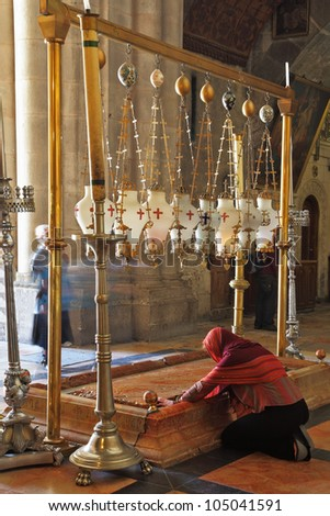 Temple of the Holy Sepulcher in Jerusalem. The oldest Christian sanctuary - Stone of Unction. The pilgrim in red clothes passionately prays under icon lamps.