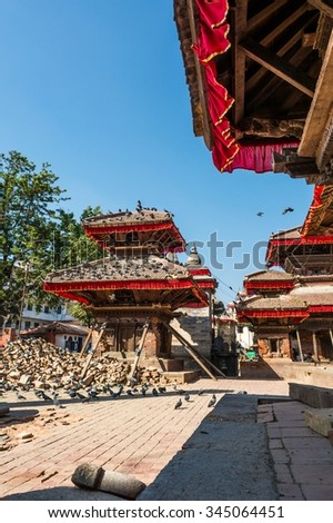 Temple supported by beams. Building damaged by earthquake at Durbar square in Kathmandu. - stock photo