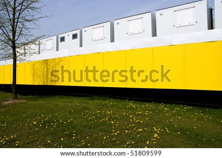 Temporary site buildings for a construction staff, behind a bright yellow security fence - stock photo