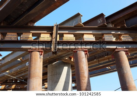 Temporary wood bracing and shims, large diameter pipes and structural steel support roadway beams before concrete is poured on bridge construction project - stock photo
