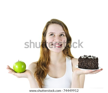 Tempted young woman holding apple and chocolate cake making a choice - stock photo