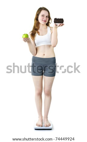 Tempted young woman holding apple and chocolate cake standing on scale
