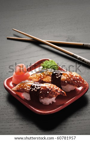 Tempting nigiri. A close-up of chopsticks and a square plate with two pieces of eel nigiri, wasabi and ginger. - stock photo