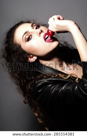 Tempting young girl with curly hair in black leather jacket licking round red lollipop standing on grey background, vertical picture - stock photo