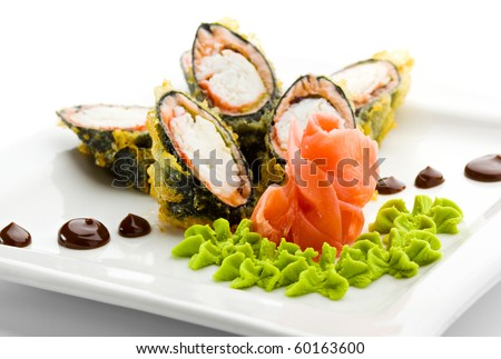 Tempura Maki Sushi - Deep Fried Roll made of Crab Meat, Salad Leaf and Unagi (eel) inside. Served with Sauce, Wasabi and Ginger - stock photo