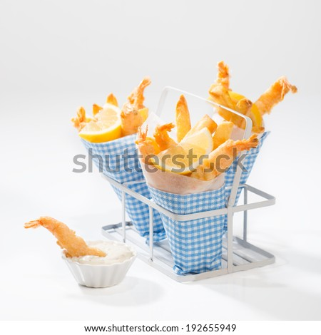 Tempura prawns with fries wrapped in cones with a dish of tartar sauce - stock photo