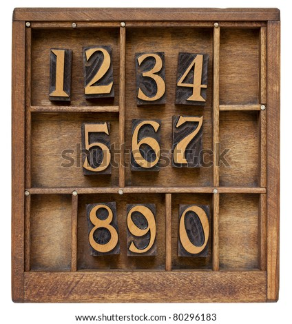 ten arabic numerals from zero to nine, vintage wood letterpress blocks stained by black ink in old typesetter case with dividers - stock photo
