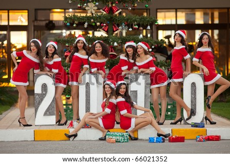 Ten beautiful sexy young women dressed as Santa posing in front of a christmas tree, shallow depth of field, focus on girls in the back