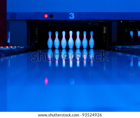 Ten bowling pins at the end of alley. Ultraviolet luminosity - stock photo
