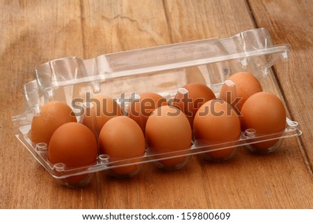 Ten brown eggs in a carton package on old table - stock photo
