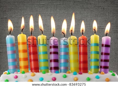 Ten colorful candles on gray background