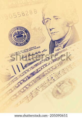 Ten Dollar Bills closeup with soft focus - design elements on vintage style. Closeup of Andrew Hamilton's portrait on a US 10 dollar banknote. American president Hamilton on the ten dollar bill. - stock photo