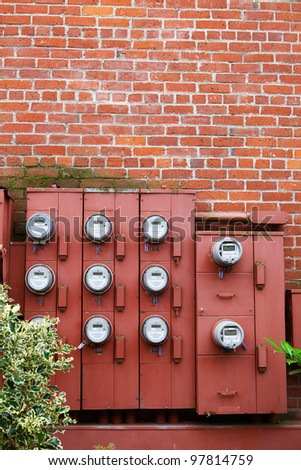 Ten Electric Meters on the red brick wall of an apartment building - stock photo