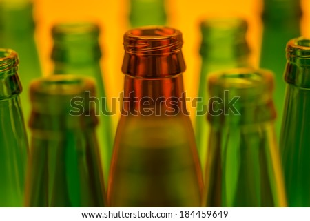Ten empty beer bottles shot with orange light. Nine green bottles and one brown.
