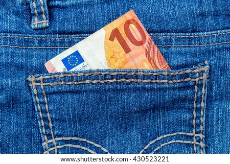 Ten Euro in  back jeans pocket, close up - stock photo