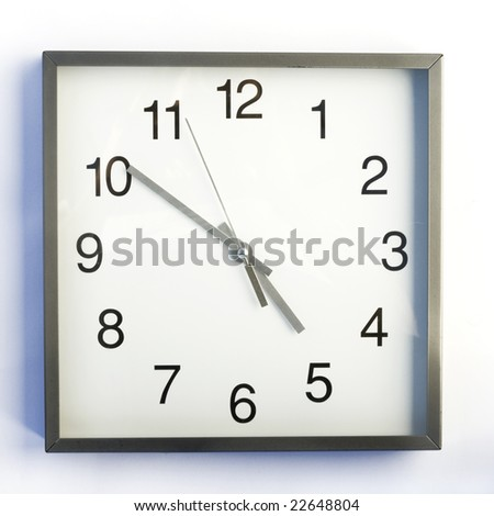 ten minutes to five. wall clock - stock photo