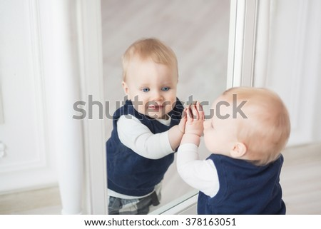 Ten month baby boy stands before the mirror and play with himself - stock photo