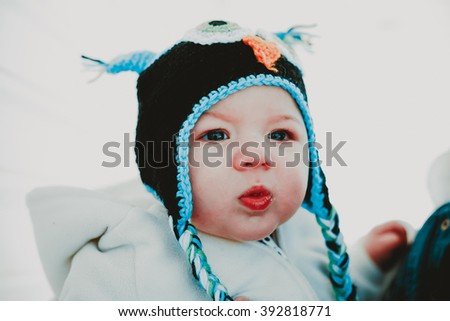 Ten month old baby boy wearing a cute knitted cap on a cold winters day