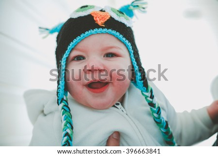 Ten month old baby boy wearing a cute knitted cap on a cold winters day - stock photo