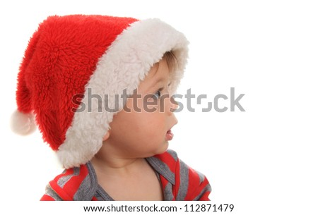 Ten month old baby boy wearing a Santa hat and looking at copy space.