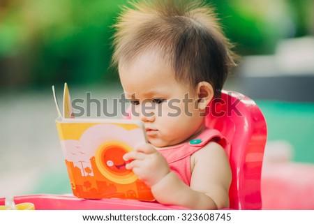 ten months baby girl reading a book in the garden. - stock photo