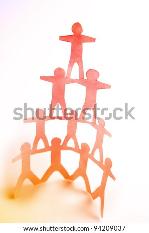 Ten paper doll people forming a human pyramid on plain background - stock photo