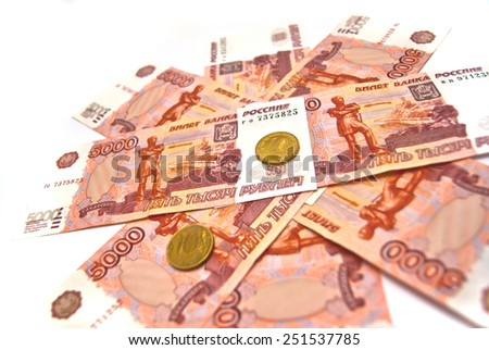 Ten rubles coins and five thousand banknotes on white - stock photo