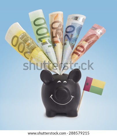 Ten,twenty,fifty,one hundred and a 200 Euro banknote in a smiling piggybank of Guinea-Bissau.(series) - stock photo