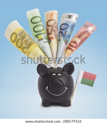 Ten,twenty,fifty,one hundred and a 200 Euro banknote in a smiling piggybank of Madagascar.(series) - stock photo