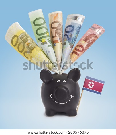 Ten,twenty,fifty,one hundred and a 200 Euro banknote in a smiling piggybank of North Korea.(series) - stock photo